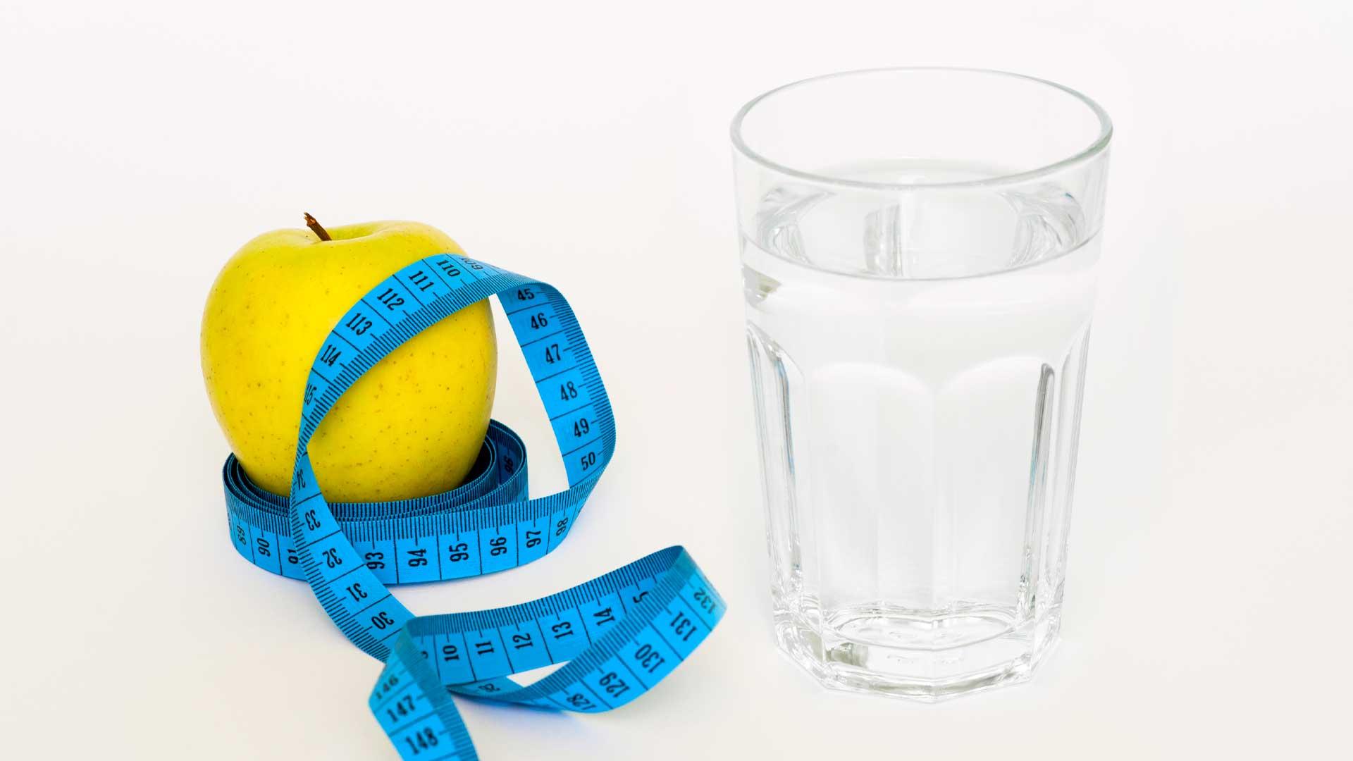Чаша вода до ябълка, увита със син сантиметър