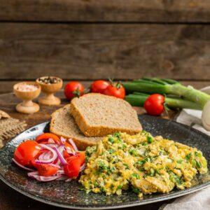 Бъркани яйца със зелен лук, поднесени със салата от домати и лук и черен хляб, снимани отстрани