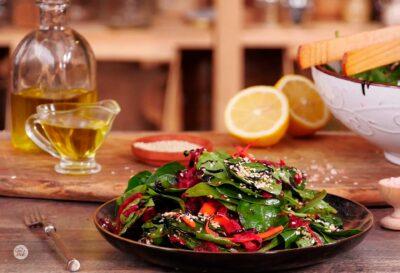 Свежа салата от листа от спанак, цвекло и моркови, в кафява чиния, поръсена със запечен сусам