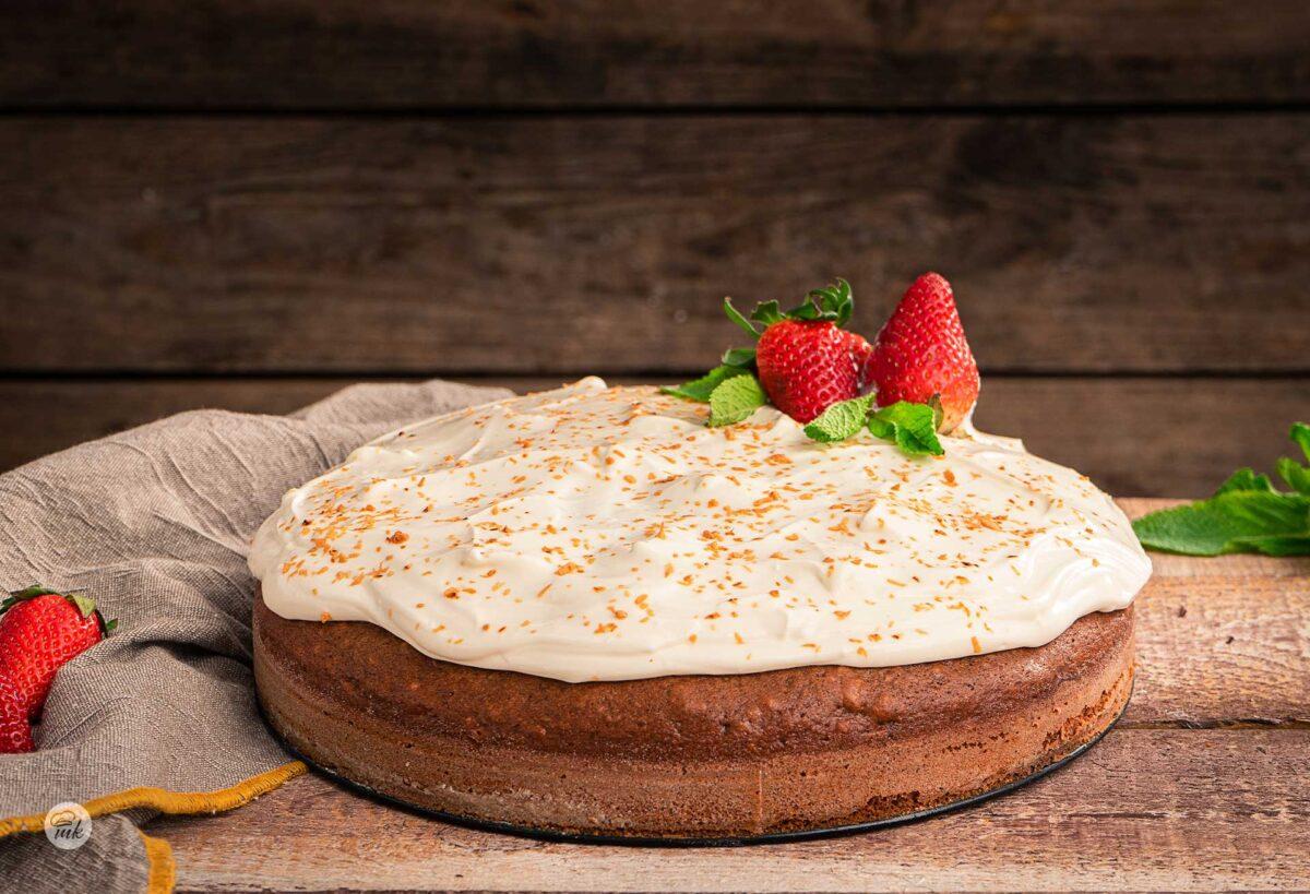 Сладкиш с кафяв блат и сметанов слой, декориран с ягоди и свежа мента