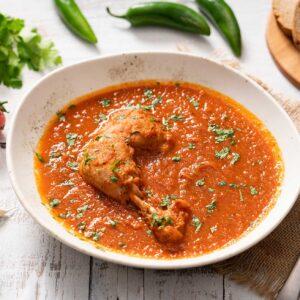 Пиле с чесново-доматен сос, поднесено в бюла чиния, снимано отгоре