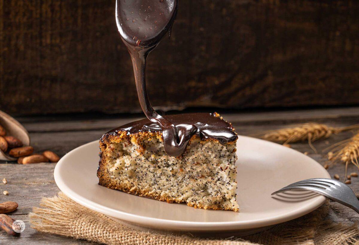 Парче сладкиш с маково семе в бяла чинийка, сниман отстрани