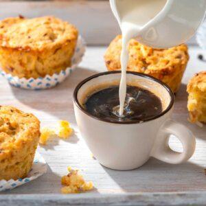 Солени мъфини с бекон на бял фон и чаша кафе в центъра