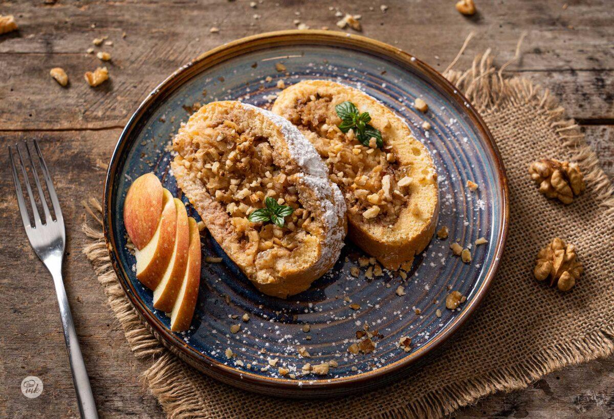 Две парчета ябълково руло със стафиди в синя чиния, снимани отгоре