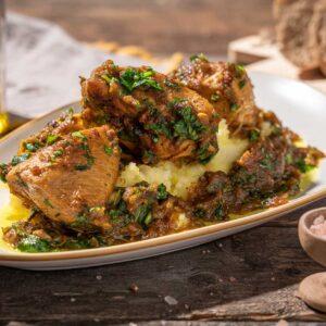 Порция задушено пиле с лук и чесън върху картофено пюре, снимано отстрани