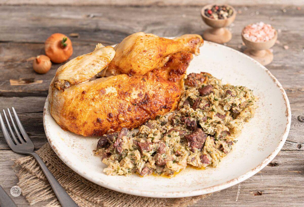 Пълнено пиле с плънка от стар хляб в бяла чиния, снимано отпред