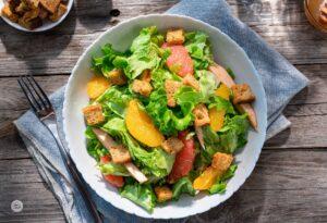 Зелена салата с портокалови филенца и пушено пиле, в бяла купа, върху текстилна кухненска подложка, снимана отгоре