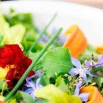 Бяла порцеланова чиния със свежа салата с цветя за ядене