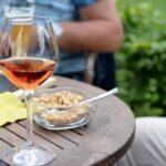 Чаша розе на дървена маса с купичка ядки до нея