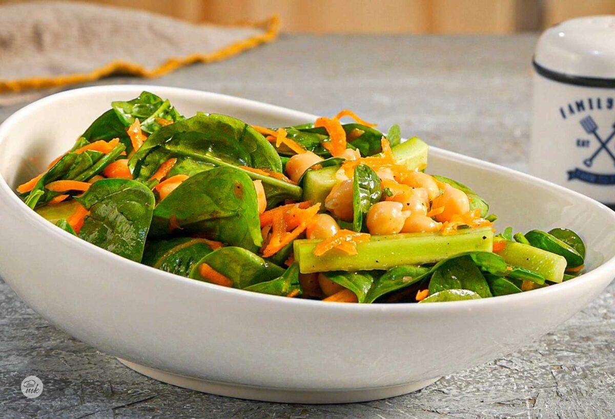 Салата от бейби спанак, морков и нахут в бяла продълговата чиния, снимана под ъгъл