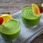 Две чаши зелено млечно смути, гарнирани с лимон и ягода