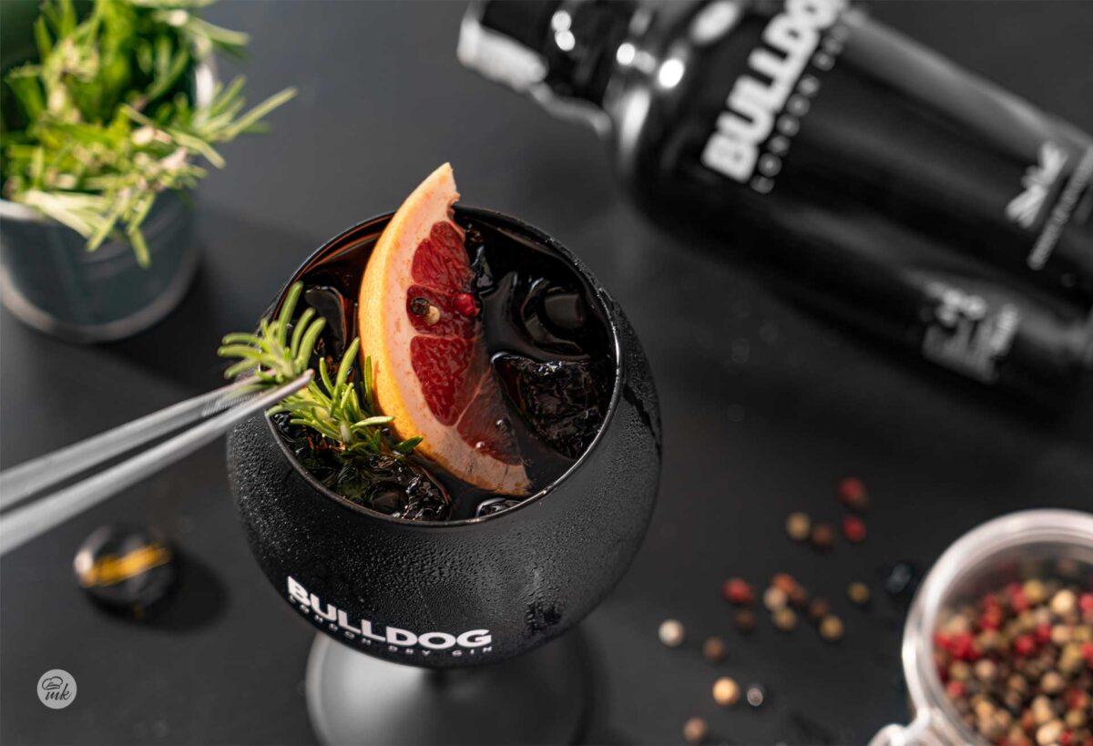 Черен фон, с черна чаша коктейл Gin and Tonic, пинсета за резен грейпфрут и бутилка, снимани отгоре