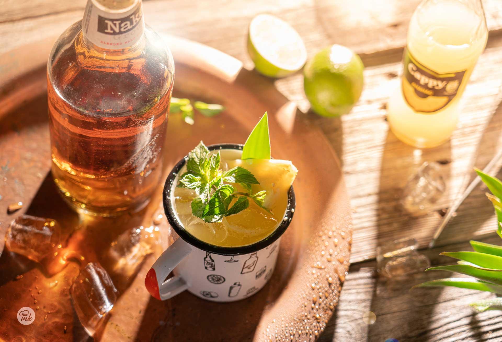 Чаша коктейл с уиски и бутилка с лайм, снимани отгоре