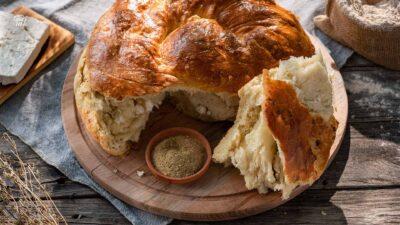 пухкава питка със сирене и шарена сол върху дървен поднос