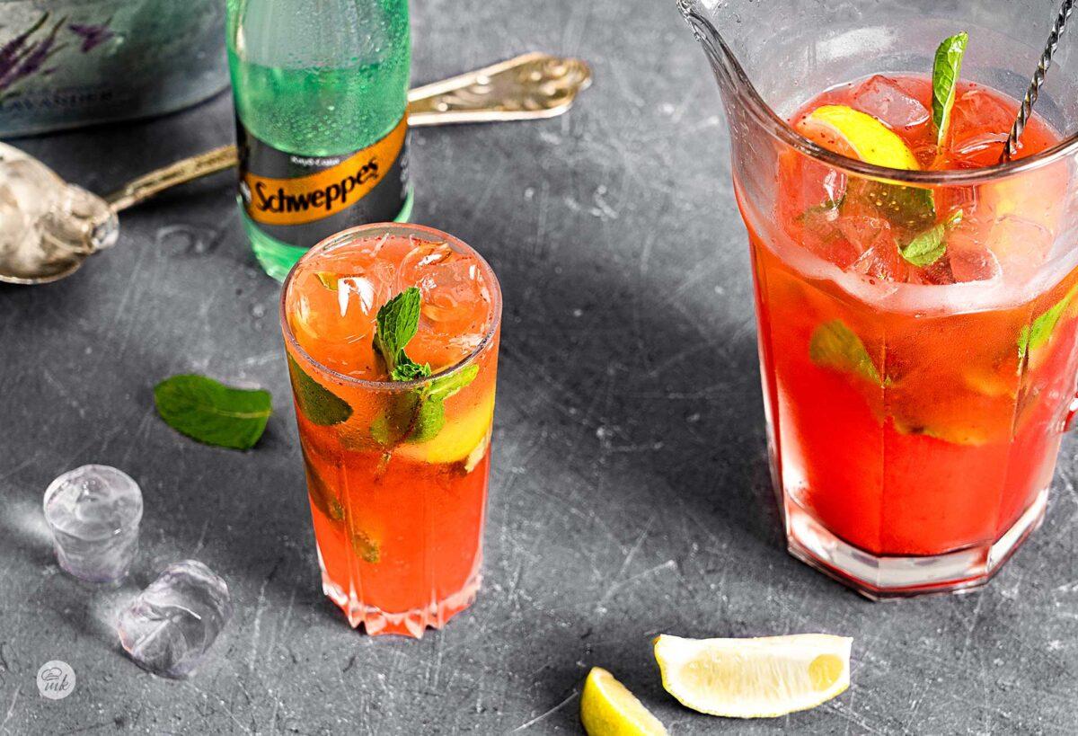 Домашна лимонада от ягоди и ананас, сервирана в чаша, кана до нея, снимана отстрани