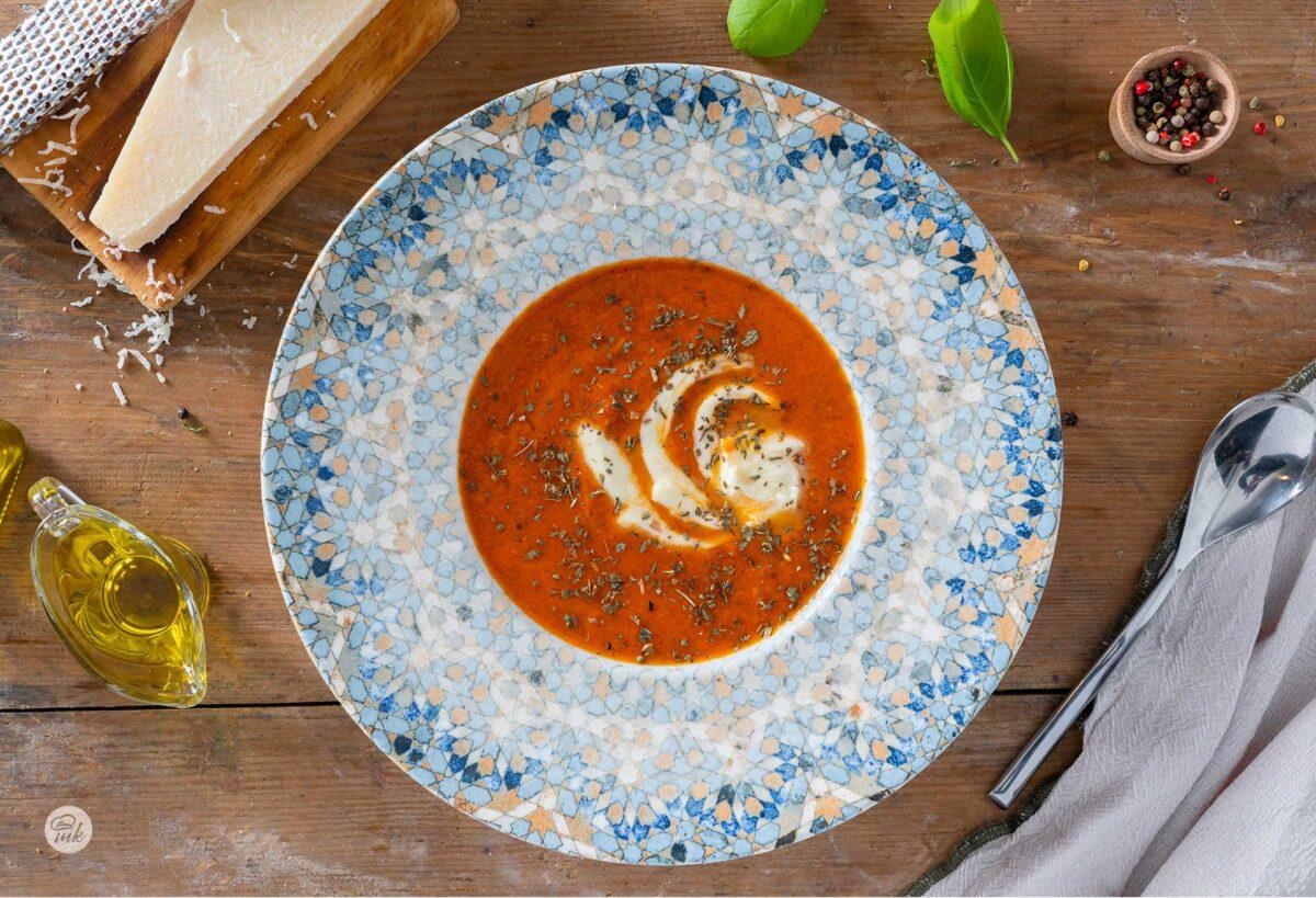Доматена крем супа с моцарела, пармезан и босилек, сервирана в купа, снимана отгоре