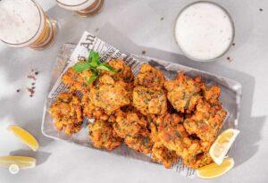 Крокети от бяла риба в правоъгълна чиния, о тях купичк с бял сос, снимани отгоре
